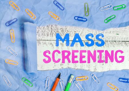 Text sign showing Mass Screening. Business photo text health evaluation performed at a large amount of population Rolled ripped torn cardboard placed above a wooden classic table backdrop