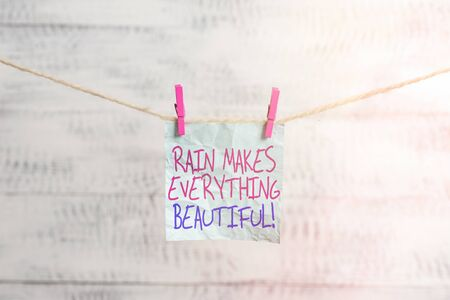 Writing note showing Rain Makes Everything Beautiful. Business concept for raining creates earth a wonderful place Clothesline clothespin rectangle shaped paper reminder white wood desk Banque d'images