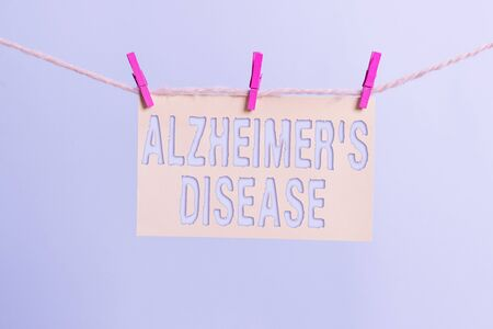 Word writing text Alzheimers Disease. Business photo showcasing irreversible brain disorder that slowly destroys memory Clothesline clothespin rectangle shaped paper reminder white wood desk