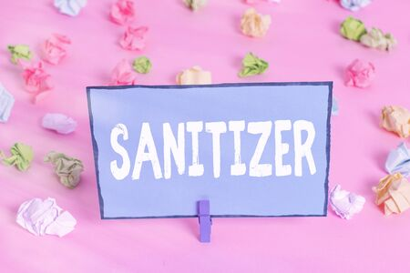 Writing note showing Sanitizer. Business concept for liquid or gel generally used to decrease infectious agents Colored crumpled papers empty reminder pink floor background clothespin