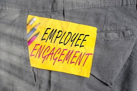 Word writing text Employee Engagement. Business photo showcasing extent to which workers feel passionate about their jobs Writing equipment and yellow note paper inside pocket of man work trousers