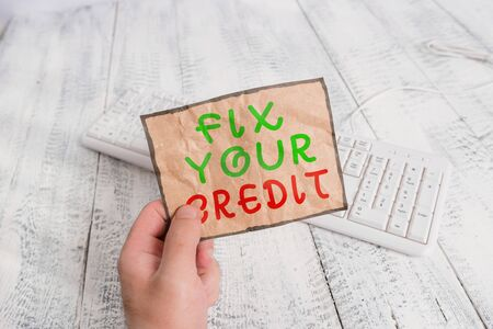 Conceptual hand writing showing Fix Your Credit. Concept meaning improve or increase your rating or score to get money loan or mortgage Man holding colorful reminder square shaped paper wood floor