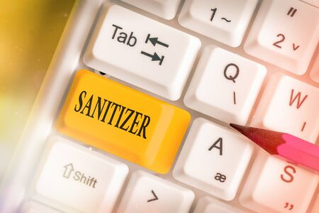 Conceptual hand writing showing Sanitizer. Concept meaning liquid or gel generally used to decrease infectious agents White pc keyboard with empty note paper above white key copy space