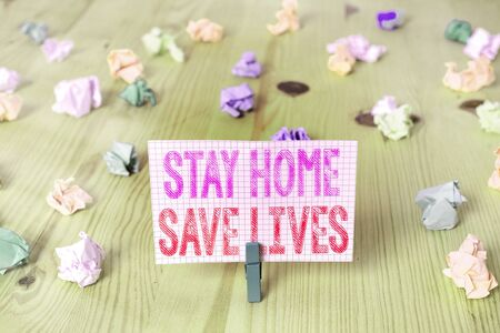 Writing note showing Stay Home Save Lives. Business concept for lessen the number of infected patients by not leaving the house Colored crumpled rectangle shaped reminder paper light blue background