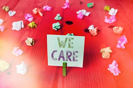 Handwriting text We Care. Conceptual photo Cherishing someones life Giving care and providing their needs Colored crumpled rectangle shaped reminder paper light blue background