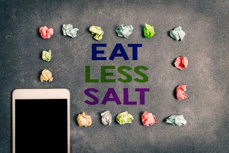 Writing note showing Eat Less Salt. Business concept for reducing the sodium intake on the food and beverages Paper accessories with smartphone arranged on different background