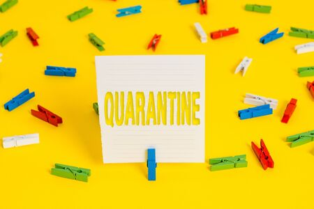 Conceptual hand writing showing Quarantine. Concept meaning restraint upon the activities of an individual or the transport of goods Colored clothespin papers empty reminder yellow floor office