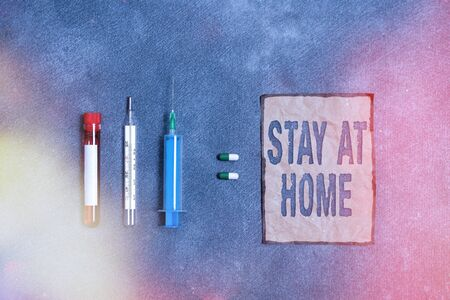 Writing note showing Stay At Home. Business concept for movement control restricting individuals from getting exposed publicly Blood sample vial medical accessories ready for examination