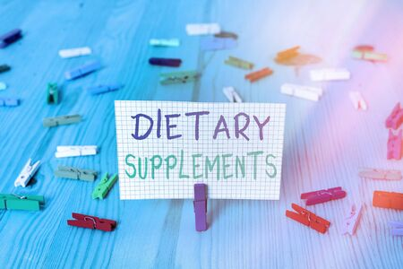 Conceptual hand writing showing Dietary Supplements. Concept meaning product intended to supplement the diet taken orally Colored crumpled rectangle shape paper light blue background