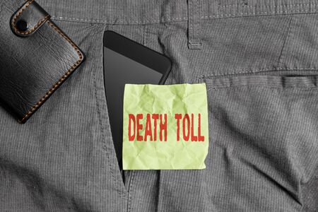 Handwriting text writing Death Toll. Conceptual photo the number of deaths resulting from a particular incident Smartphone device inside trousers front pocket with wallet and note paper