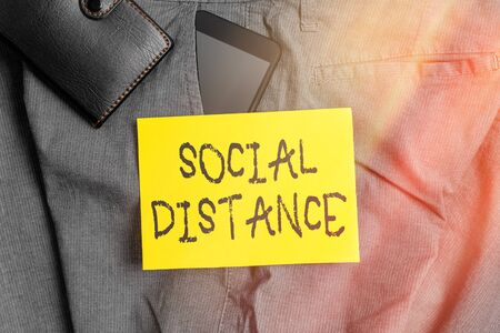 Word writing text Social Distance. Business photo showcasing degree of acceptance of general interaction of individuals Smartphone device inside trousers front pocket with wallet and note paper