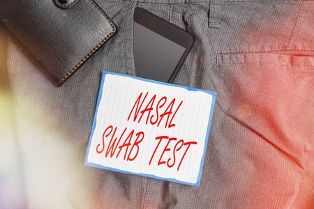 Text sign showing Nasal Swab Test. Business photo showcasing diagnosing an upper respiratory tract infection through nasal secretion Smartphone device inside trousers front pocket with wallet and note paper