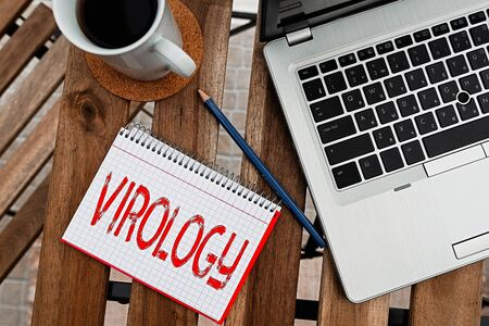 Writing note showing Virology. Business concept for branch of science dealing with the variety of viral agents and disease Workplace overview with laptop used for individual interest