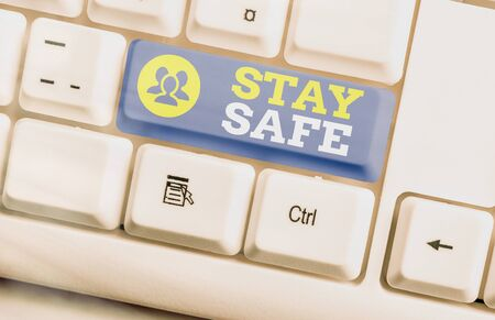 Text sign showing Stay Safe. Business photo text secure from threat of danger, harm or place to keep articles White pc keyboard with empty note paper above white key copy space