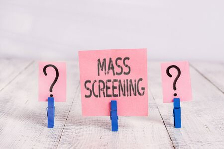 Text sign showing Mass Screening. Business photo showcasing health evaluation performed at a large amount of population Scribbled and crumbling sheet with paper clips placed on the wooden table 스톡 콘텐츠