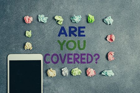 Writing note showing Are You Covered Question. Business concept for asking if they had insurance in work or life Paper accessories with smartphone arranged on different background