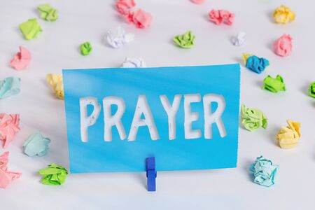 Writing note showing Prayer. Business concept for solemn request for help or expression of thanks addressed to God Colored crumpled paper empty reminder white floor clothespin
