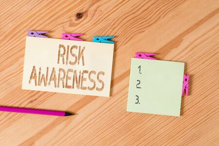 Writing note showing Risk Awareness. Business concept for recognizing factors that may cause a lifethreatening effect Colored clothespin papers empty reminder wooden floor background office