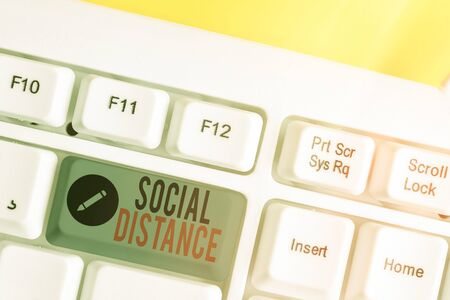 Text sign showing Social Distance. Business photo text degree of acceptance of general interaction of individuals White pc keyboard with empty note paper above white key copy space