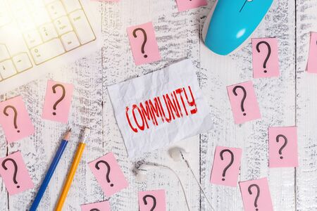 Text sign showing Community. Business photo text group of showing with a common characteristics living together Writing tools, computer stuff and scribbled paper on top of wooden table