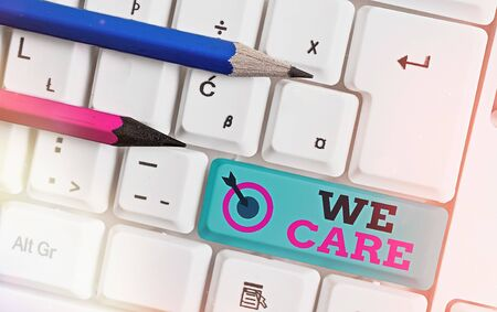 Text sign showing We Care. Business photo text Cherishing someones life Giving care and providing their needs White pc keyboard with empty note paper above white key copy space 版權商用圖片