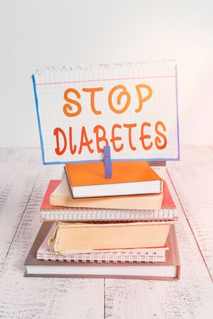 Text sign showing Stop Diabetes. Business photo text prevent the disease of elevated glucose level in the blood pile stacked books notebook pin clothespin colored reminder white wooden