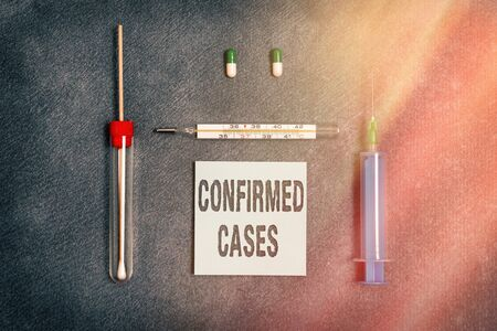 Handwriting text writing Confirmed Cases. Conceptual photo set of circumstances or conditions requiring action Set of medical equipment with notepad for health condition assessment Reklamní fotografie