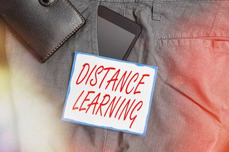 Text sign showing Distance Learning. Business photo showcasing educational lectures broadcasted over the Internet remotely Smartphone device inside trousers front pocket with wallet and note paper Banco de Imagens