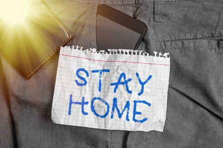 Word writing text Stay Home. Business photo showcasing not go out for an activity and stay inside the house or home Smartphone device inside trousers front pocket with wallet and note paper Stock Photo