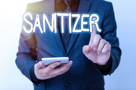 Writing note showing Sanitizer. Business concept for liquid or gel generally used to decrease infectious agents Model with pointing hand finger symbolizing navigation progress growth 스톡 콘텐츠