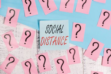 Word writing text Social Distance. Business photo showcasing degree of acceptance of general interaction of individuals Scribbled and crumbling papers with thick cardboard above wooden table