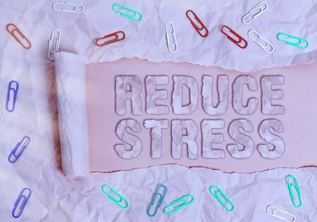 Conceptual hand writing showing Reduce Stress. Concept meaning to lessen the state of mental or emotional strain or tension Rolled ripped torn cardboard above a wooden classic table