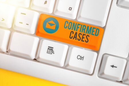 Text sign showing Confirmed Cases. Business photo text set of circumstances or conditions requiring action White pc keyboard with empty note paper above white key copy space