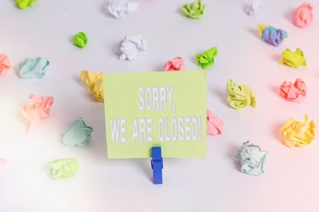 Word writing text Sorry, We Are Closed. Business photo showcasing apologize for shutting off business for specific time Colored crumpled papers empty reminder white floor background clothespin