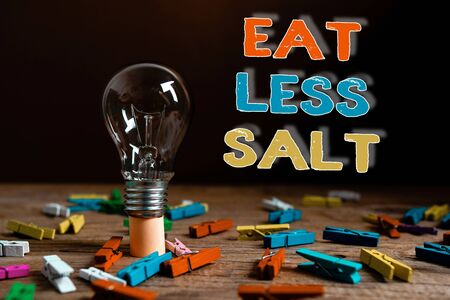 Conceptual hand writing showing Eat Less Salt. Concept meaning reducing the sodium intake on the food and beverages Realistic colored vintage light bulbs, idea sign solution Foto de archivo