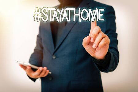 Handwriting text Hashtag Stay at home. Conceptual photo a trending label in social media related to the coronvirus outbreak Model with pointing hand finger symbolizing navigation progress growth