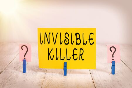 Conceptual hand writing showing Invisible Killer. Concept meaning presence into the air of a substance which are harmful Crumbling sheet with paper clips placed on the wooden table