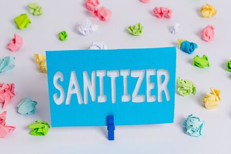 Writing note showing Sanitizer. Business concept for liquid or gel generally used to decrease infectious agents Colored crumpled paper empty reminder white floor clothespin 스톡 콘텐츠