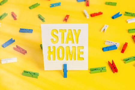 Conceptual hand writing showing Stay Home. Concept meaning not go out for an activity and stay inside the house or home Colored clothespin papers empty reminder yellow floor office