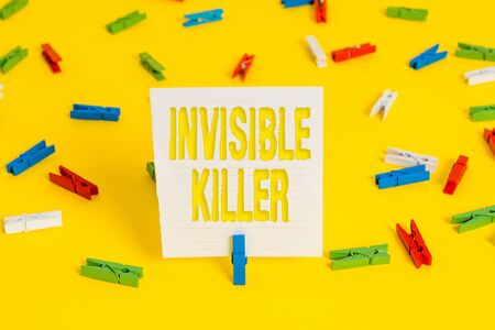 Conceptual hand writing showing Invisible Killer. Concept meaning presence into the air of a substance which are harmful Colored clothespin papers empty reminder yellow floor office