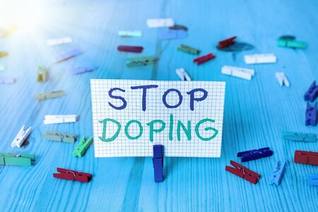 Conceptual hand writing showing Stop Doping. Concept meaning quit the use of banned athletic performanceenhancing drugs Colored crumpled rectangle shape paper light blue background