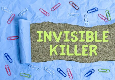 Conceptual hand writing showing Invisible Killer. Concept meaning presence into the air of a substance which are harmful Rolled ripped torn cardboard above a wooden classic table Stock Photo