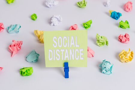 Word writing text Social Distance. Business photo showcasing degree of acceptance of general interaction of individuals Colored crumpled papers empty reminder white floor background clothespin