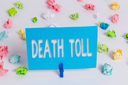 Writing note showing Death Toll. Business concept for the number of deaths resulting from a particular incident Colored crumpled paper empty reminder white floor clothespin