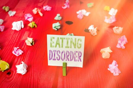 Handwriting text Eating Disorder. Conceptual photo illnesses or severe disturbances in their eating behaviors Colored crumpled rectangle shaped reminder paper light blue background