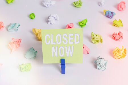Word writing text Closed Now. Business photo showcasing of a business having ceased trading especially for a short period Colored crumpled papers empty reminder white floor background clothespin