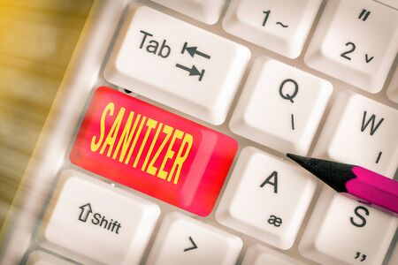 Writing note showing Sanitizer. Business concept for liquid or gel generally used to decrease infectious agents White pc keyboard with empty note paper above white key copy space