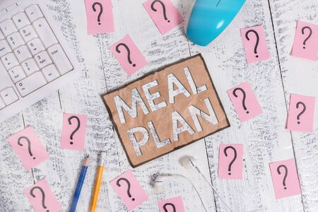 Conceptual hand writing showing Meal Plan. Concept meaning act of taking time to plan any number of meals for the week Writing tools and scribbled paper on top of the wooden table