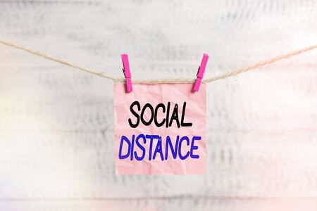 Conceptual hand writing showing Social Distance. Concept meaning degree of acceptance of general interaction of individuals Clothespin rectangle shaped paper reminder white wood desk
