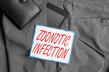 Text sign showing Zoonotic Infection. Business photo showcasing communicable disease transmitted by a non viral agent Smartphone device inside trousers front pocket with wallet and note paper